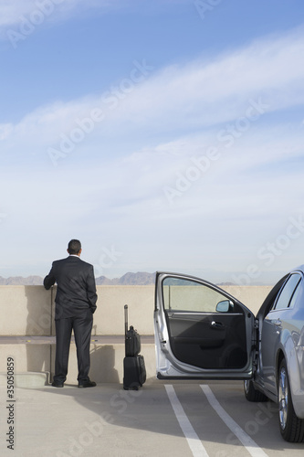 Businessman standing in parking lot with car and luggage