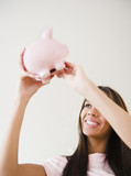 Hispanic teenage girl lifting piggy bank