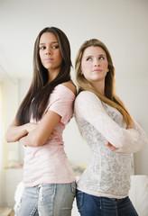 Teenage girls standing back to back