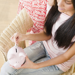 Hispanic teenage girl putting coin into piggy bank