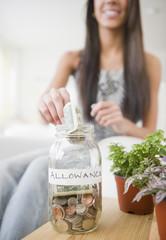 Hispanic teenager putting money into allowance jar