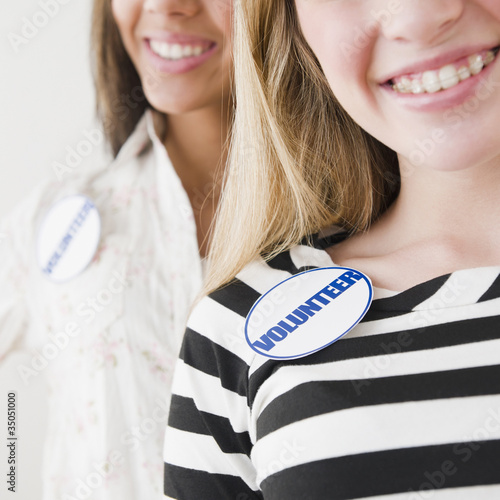 Teenage girls wearing volunteer badges