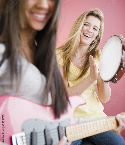 Teenage girls playing guitar and tambourine