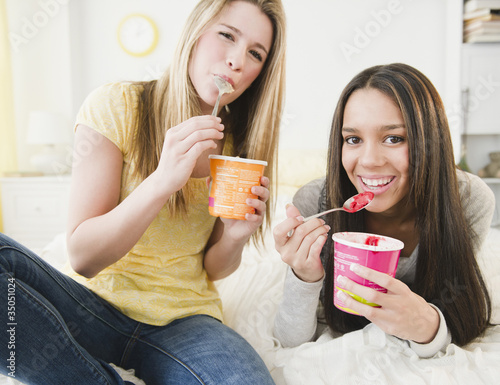 Teenage girls eating ice cream together