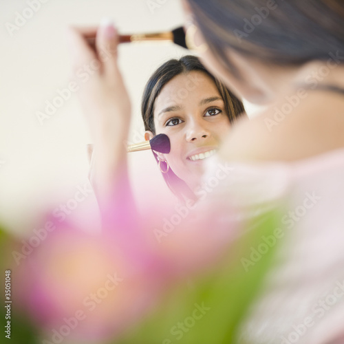 Hispanic teenager putting on blush