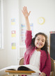 Hispanic girl raising hand in classroom