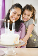 Mother and daughter standing with birthday cake