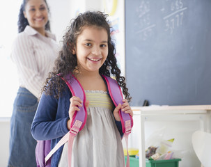 Smiling Hispanic girl with backpack in classroom