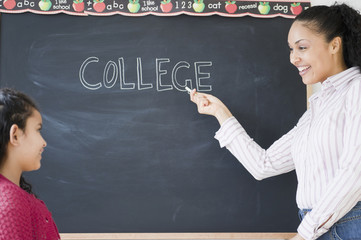 "Girl watching teacher write the word ""college"" on blackboard"