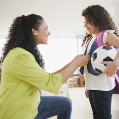 Mother dressing daughter holding soccer ball
