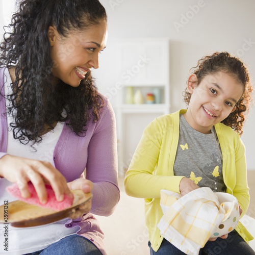 Mother and daughter drying dishes together