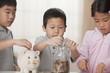 Korean children putting coins in piggy bank