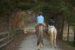 Caucasian girl and trainer riding horses