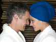 Caucasian couple in robes smiling at each other