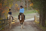 Caucasian girl and trainer riding horses