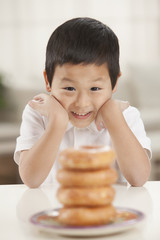 Korean boy looking at stack of donuts