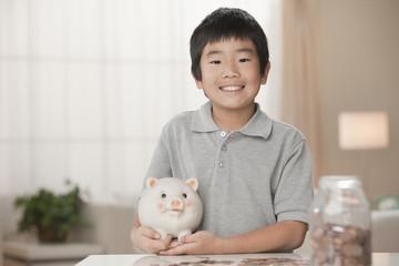 Korean boy putting coins in piggy bank