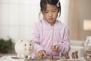 Korean girl putting coins in piggy bank