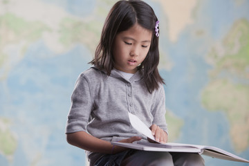 Korean girl reading book near map