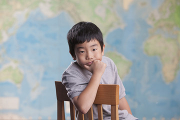 Korean boy sitting in chair near map
