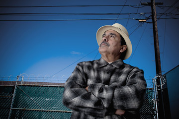 Hispanic man with arms crossed looking up