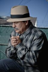 Serious Hispanic man praying
