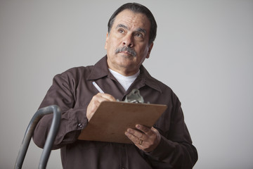 Hispanic man writing on clipboard
