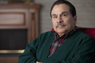 Hispanic man sitting in chair