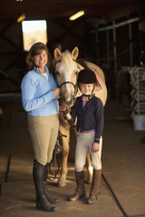 Caucasian girl and trainer standing with horse