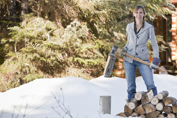 Caucasian woman chopping firewood in snow