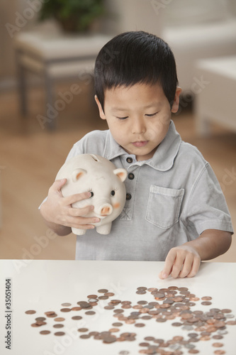 Korean boy putting coins in piggy bank