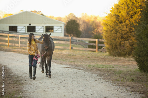 Caucasian girl leading horse on path