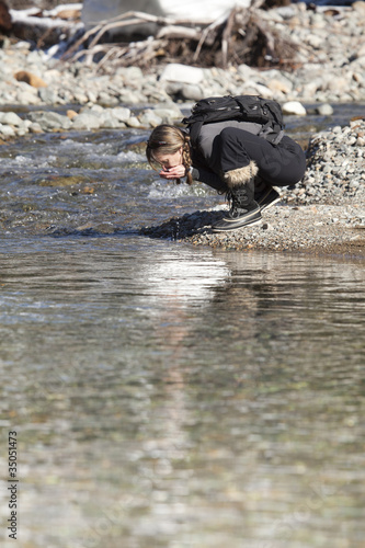 Caucasian hiker drinking from remote stream