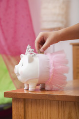 African American girl putting coin into piggy bank