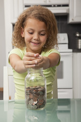 African American girl putting coins in jar