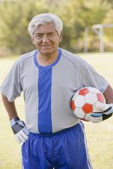 Senior Chilean soccer player holding soccer ball