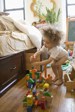 Mixed race boy playing with building blocks in bedroom