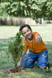 Hispanic boy planting tree and giving thumbs up