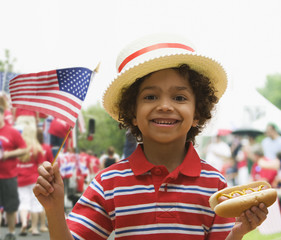 Mixed race boy eating hot dog at fourth of July celebration