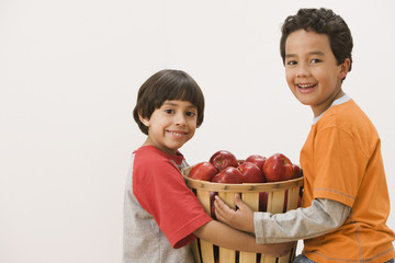 Hispanic brothers carrying basket of apples