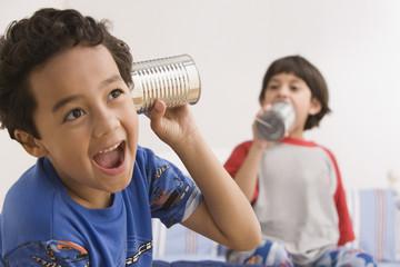 Hispanic brothers using tin can telephone