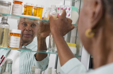 Black woman taking medication from cabinet