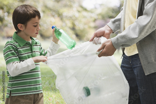 Caucasian father and son picking up litter together