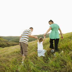 Family holding hands and walking up field