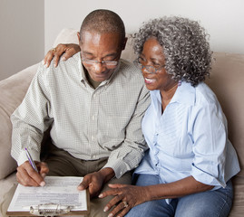 African American couple filling out form on clipboard together