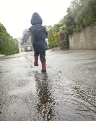 Caucasian boy walking in rain puddle