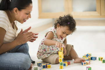 Hispanic mother watching daughter playing with alphabet blocks