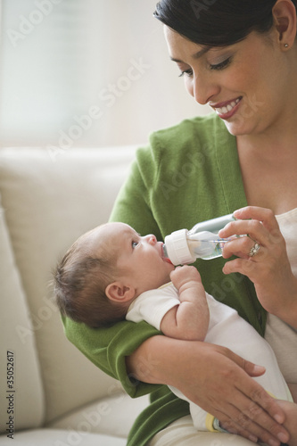 Hispanic mother feeding newborn baby girl