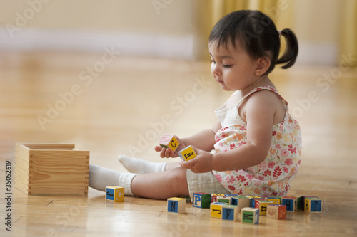 Hispanic girl sitting on floor playing with alphabet blocks