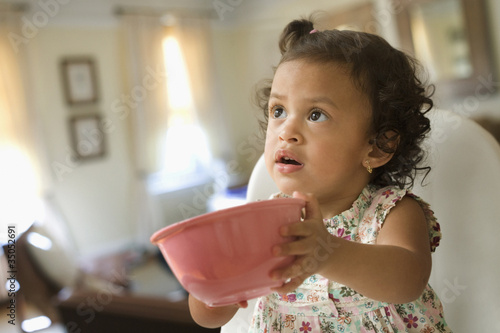 Hispanic girl holding out bowl